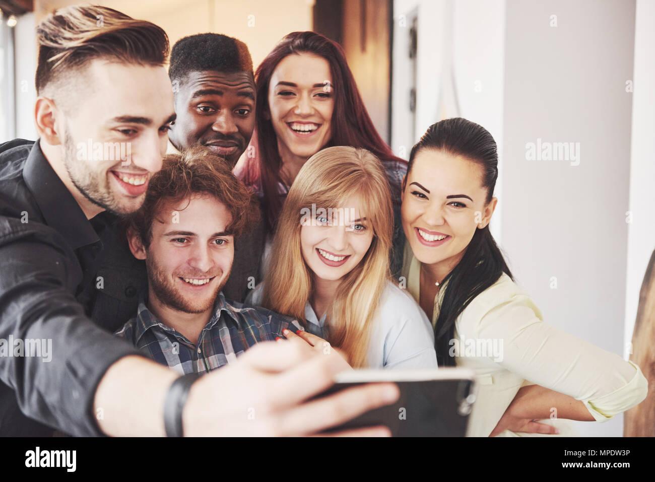 Amigos divirtiéndose en el restaurante.cuatro chicas y dos chicos haciendo selfie potable, hacer la paz firme y riendo. Mujer sosteniendo en primer plano en el teléfono inteligente. Vestir ropa casual Imagen De Stock