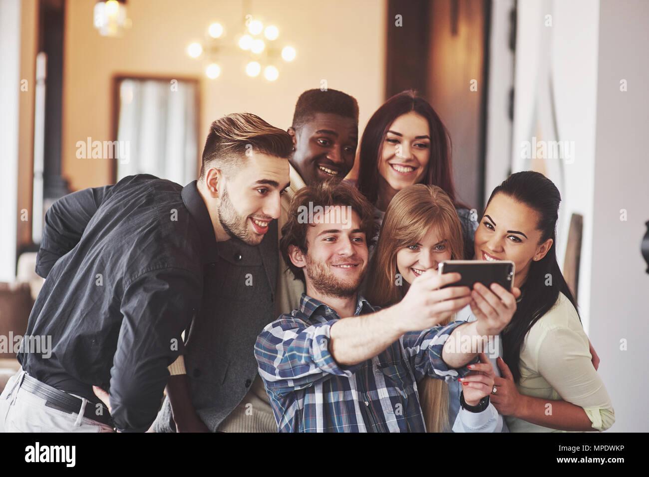 Población multirracial divirtiéndose en el cafe tomando un selfie con teléfono móvil. Grupo de jóvenes amigos sentado en el restaurante tomando autorretrato con teléfonos inteligentes. Imagen De Stock