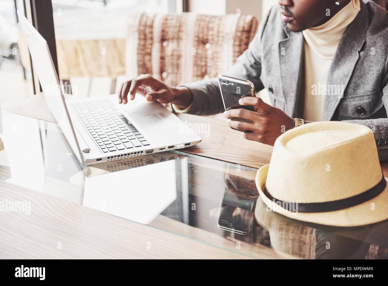 Pensativo afro americana guapo escritor profesional artículos populares en el blog de moda vestidos de traje y gafas pensando sobre historia nueva corrección de su script desde portátil sentado en el cafe Imagen De Stock
