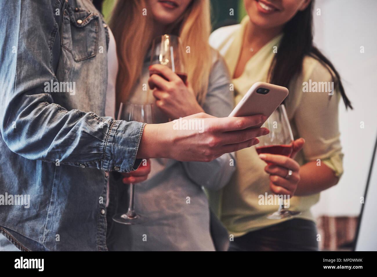 Presentando una imagen feliz grupo de amigas con vino tinto. Juntos, ver una foto en un smartphone Imagen De Stock