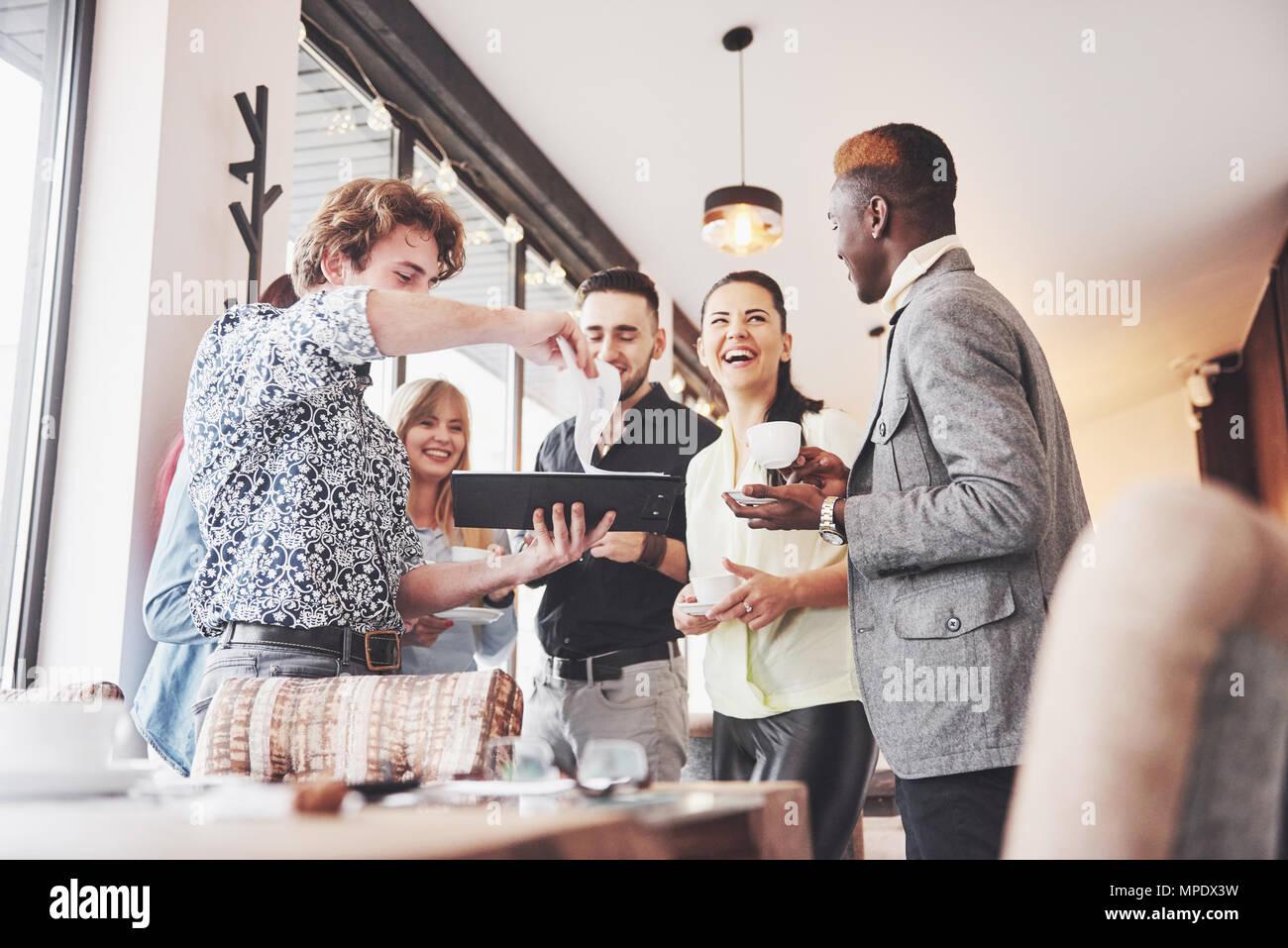 Jóvenes empresarios exitosos están hablando y sonriendo durante la pausa para el café en la oficina Imagen De Stock