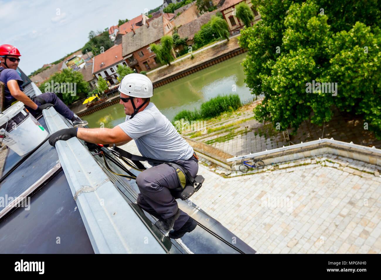 Escalador, alpinista industrial, se pasa por el borde del techo. Él es bajar a lavar el edificio. Foto de stock