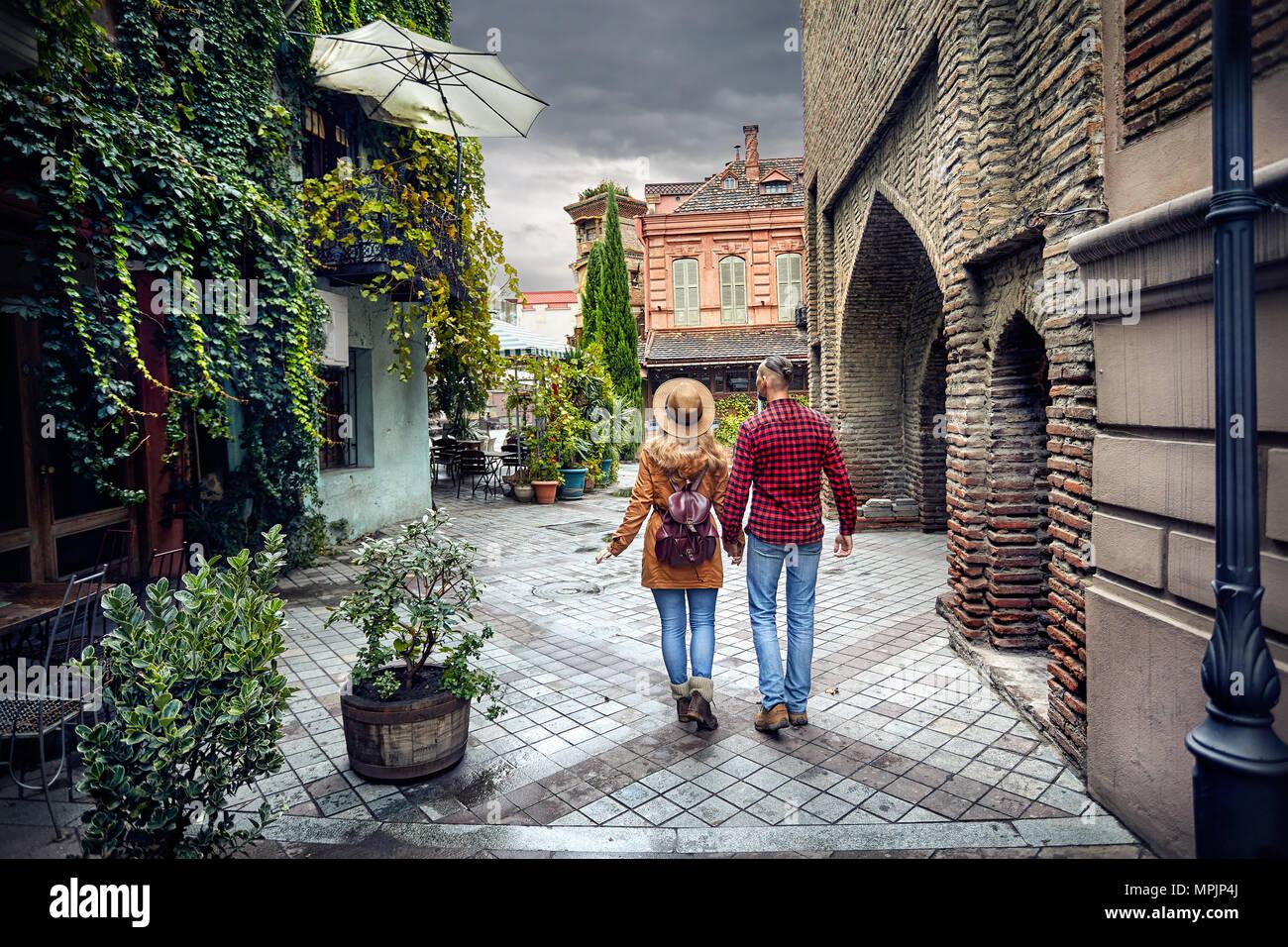 Turismo en la mujer y el hombre en sombrero marrón camiseta roja caminando por las antiguas calles de viejo Tbilisi, Georgia central Imagen De Stock