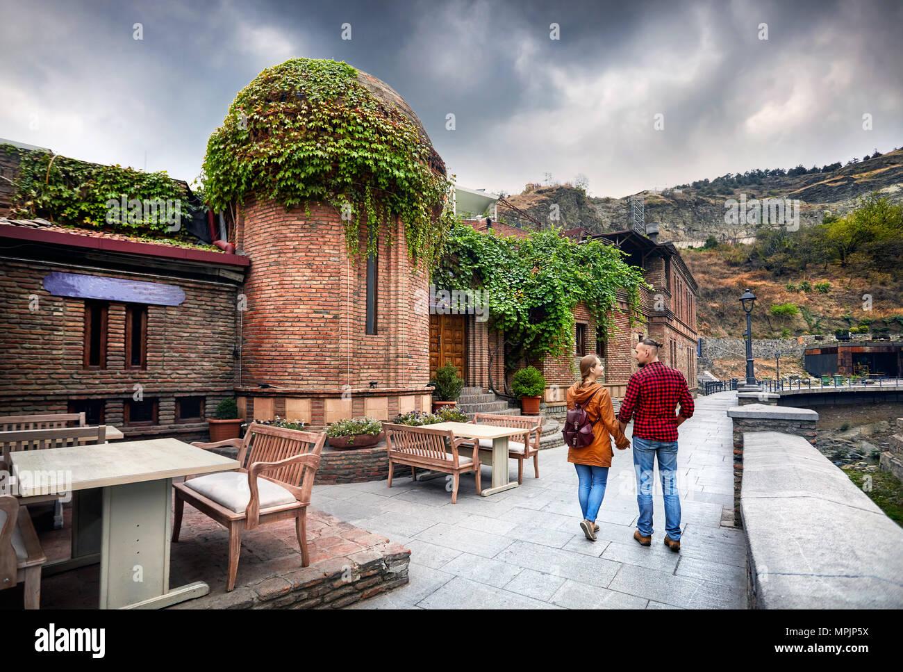 Turismo en la mujer y el hombre en chaqueta marrón camiseta roja caminando por las antiguas calles de baño sulfúrico público en el centro de distrito de Tbilisi, Georgia Imagen De Stock