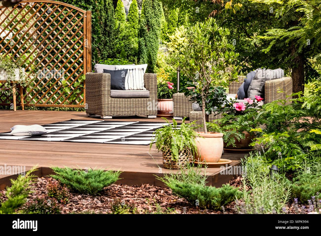 Jardín Con Mesas Y Sillas De Mimbre En Una Terraza Decorada