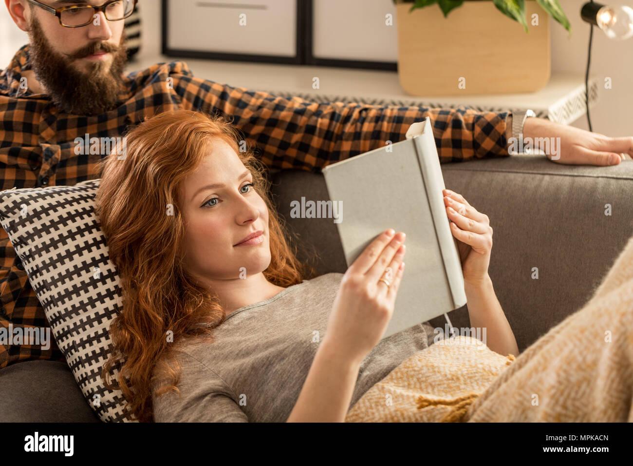 Pelirroja mujer leyendo un libro sentado detrás de ella y su marido. Foto de stock