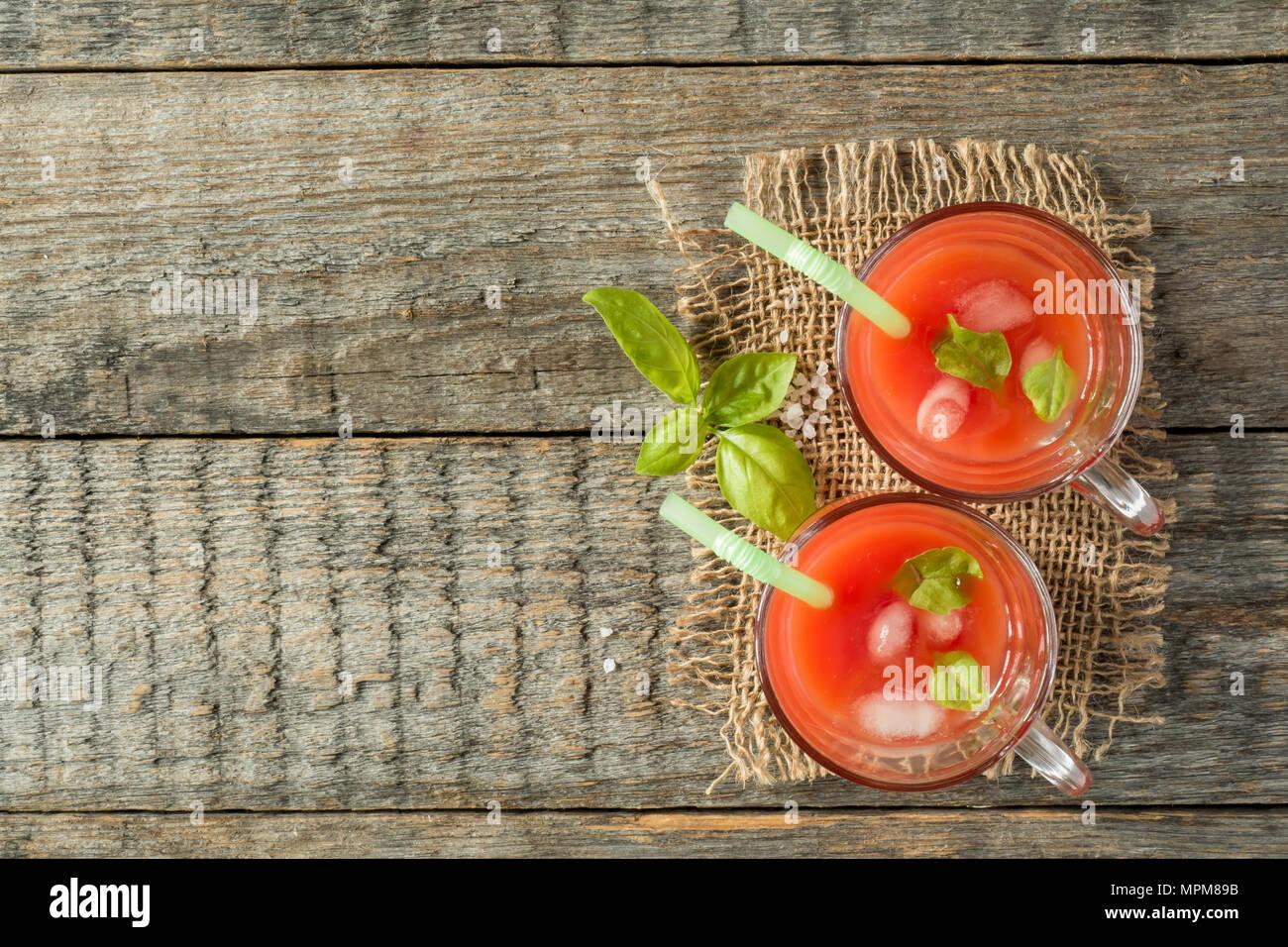 Cóctel rojo con jugo de tomate, albahaca y sal, el enfoque selectivo. Imagen De Stock