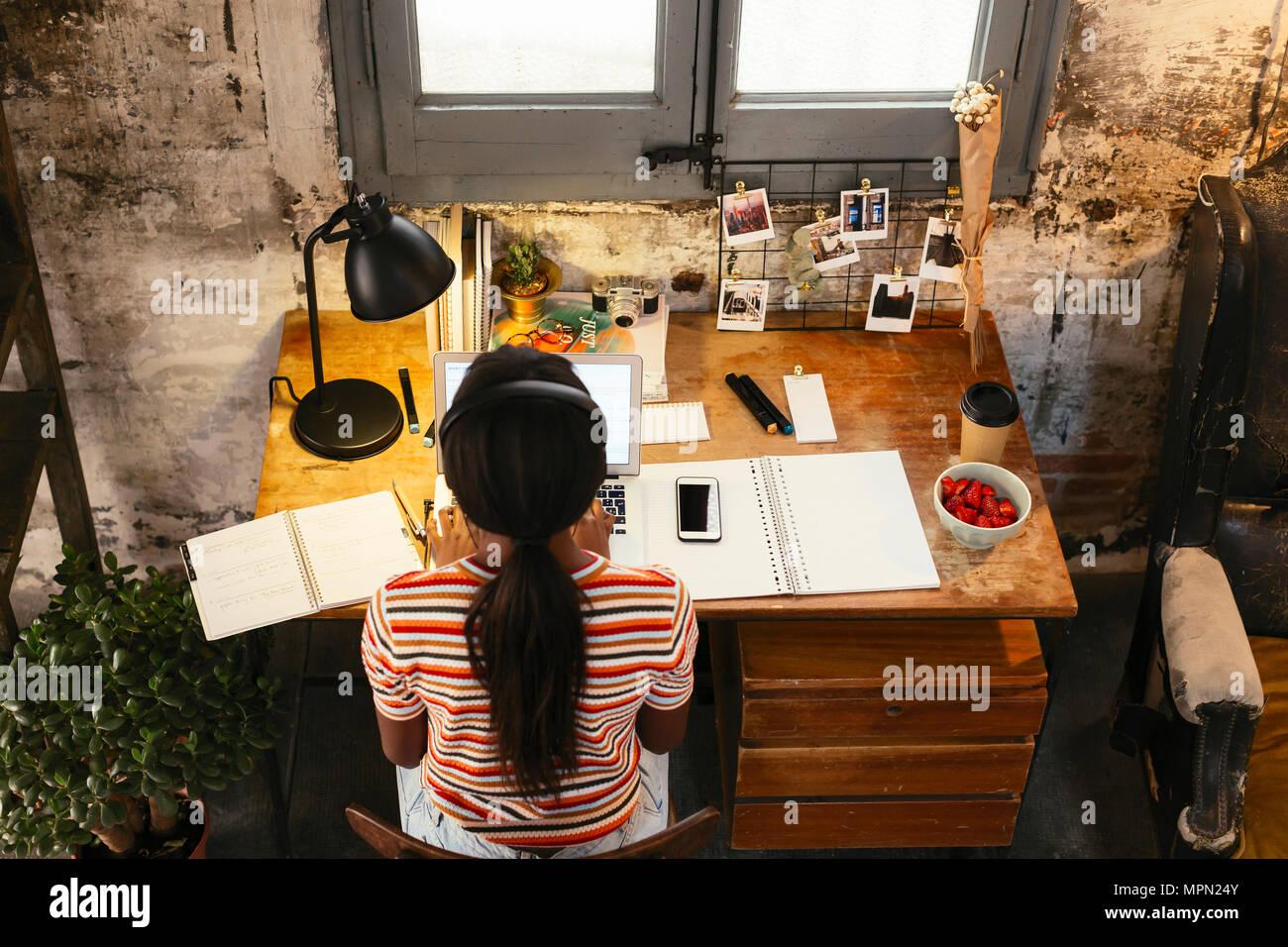 Vista posterior del joven sentado en un escritorio en un loft trabajando en el portátil visto desde arriba Imagen De Stock