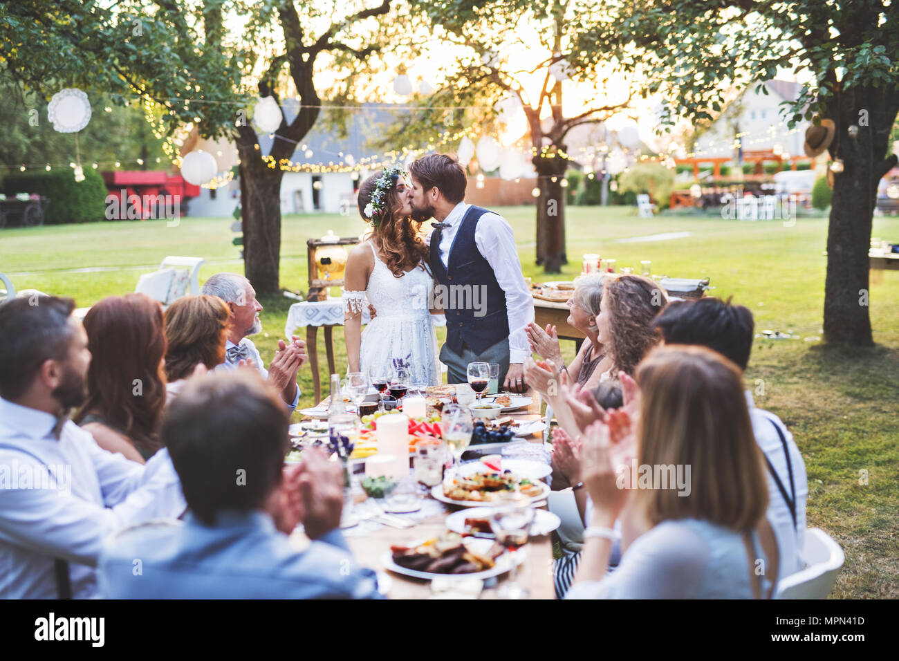 La novia y el novio con los huéspedes en la recepción de la boda fuera en el patio. Imagen De Stock