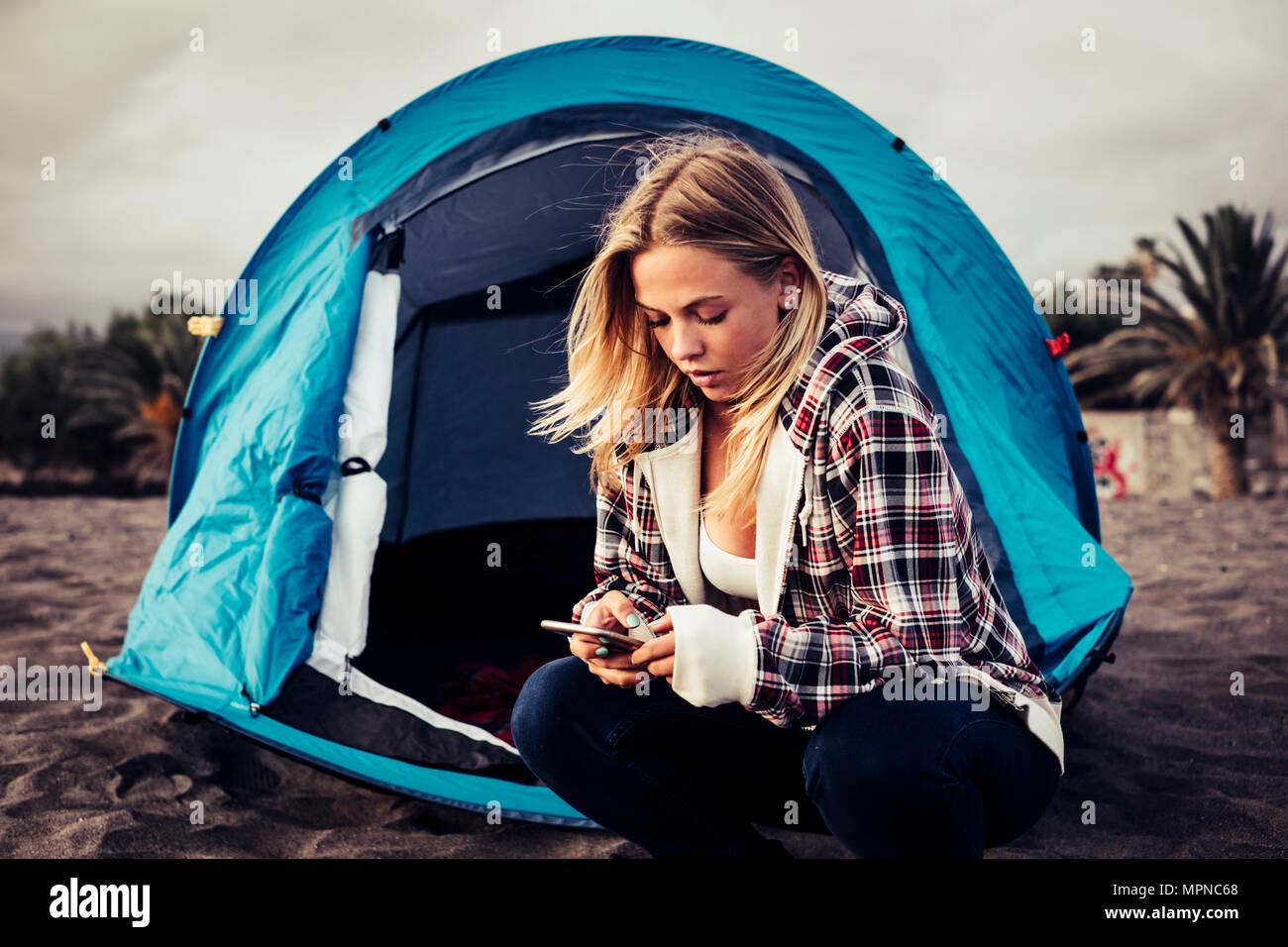 Siempre conectado con tecnología joven rubia permanecer fuera de su tienda de campaña en la playa para gozar de la libertad de trabajo. Imagen De Stock