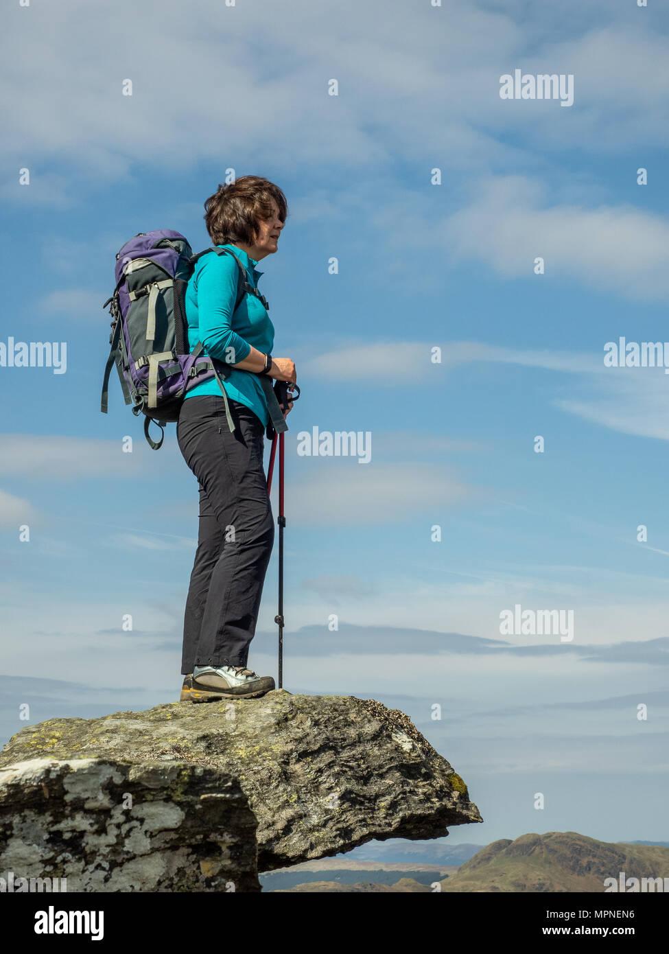 Una dama senior activo de pie sobre las rocas en la cima de una montaña en las Highlands escocesas en un cálido día de primavera Imagen De Stock