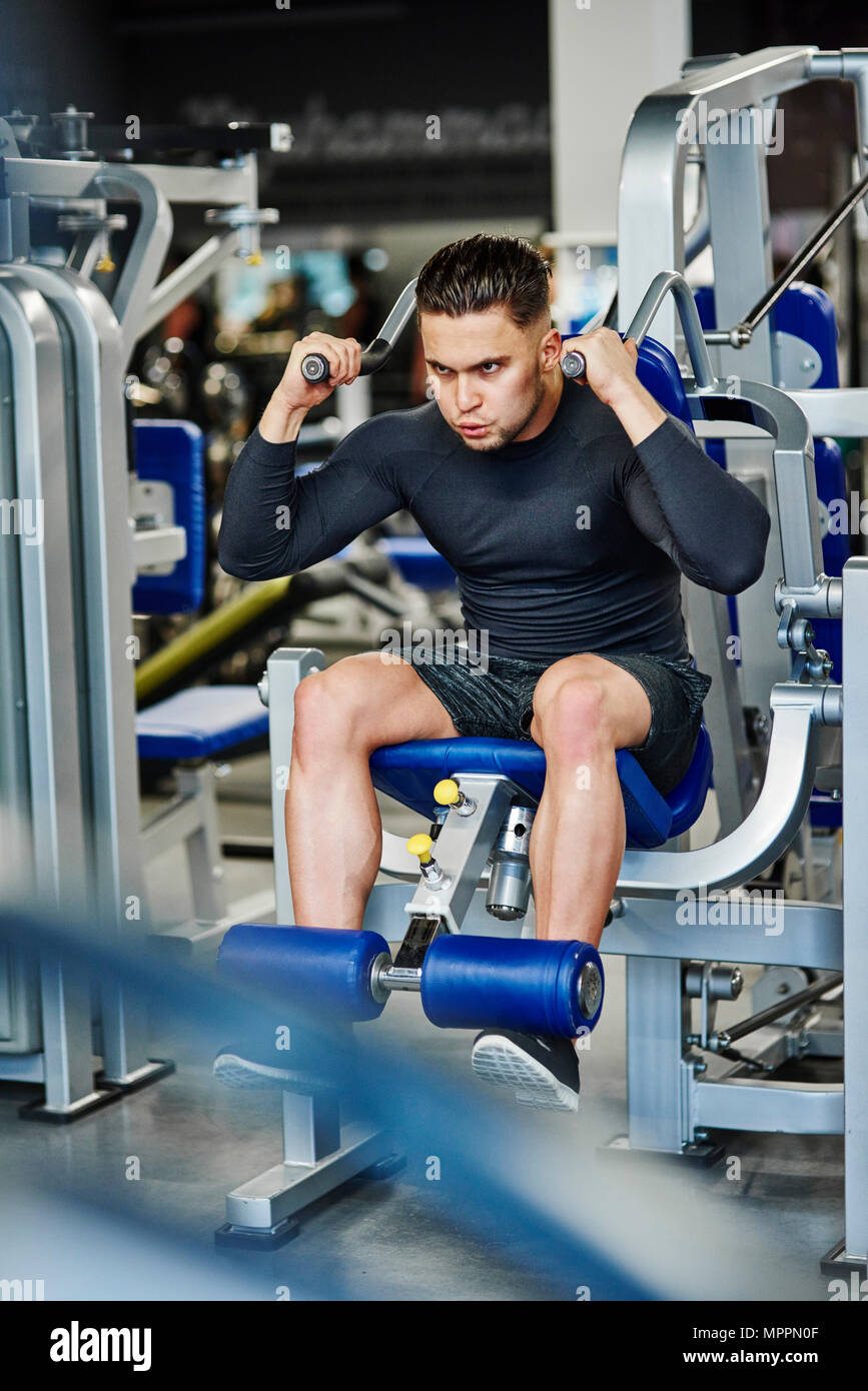 El hombre la formación con máquina de ejercicio en el gimnasio. Imagen De Stock