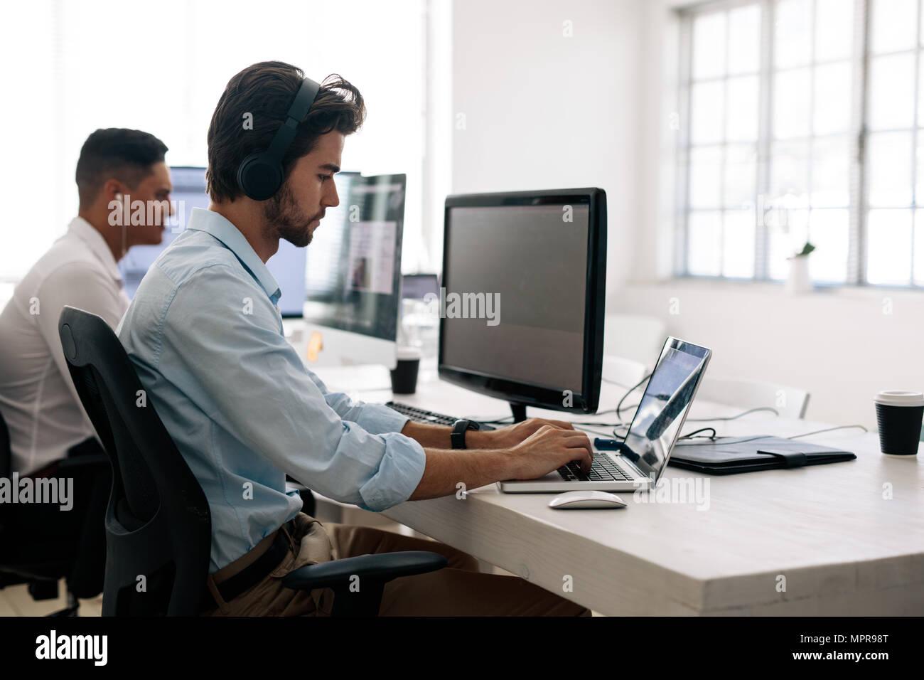 Los desarrolladores de software sentado en la oficina trabajando en equipos que lleva puestos los auriculares. El desarrollador de la aplicación trabajando en un portátil en la oficina. Imagen De Stock