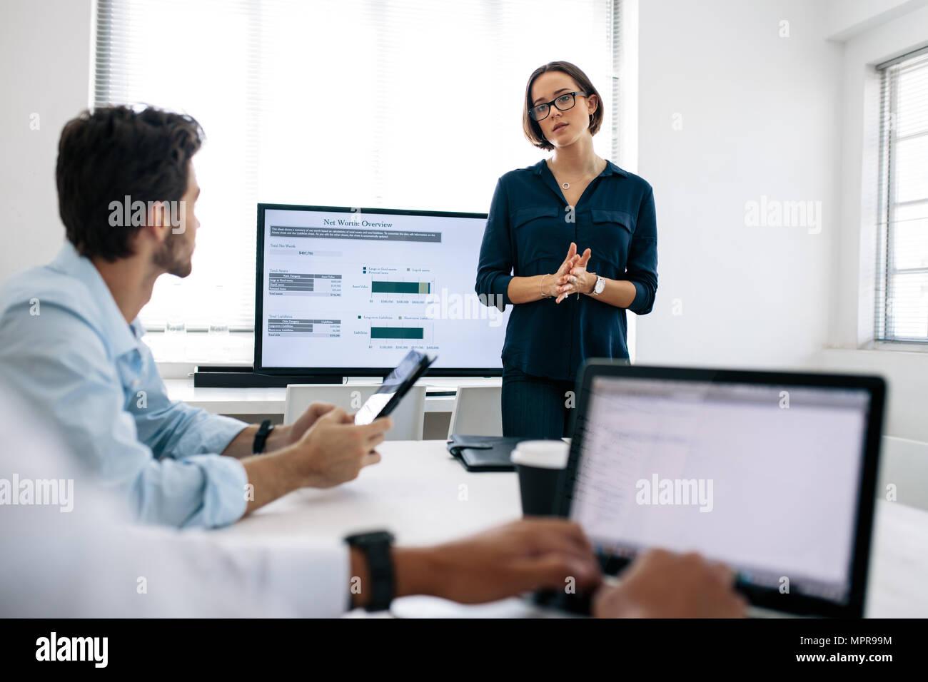 La empresaria de llevar gafas haciendo una presentación a sus colegas en la oficina. Colegas de la Oficina mirando ordenadores portátiles mientras escucha un Imagen De Stock