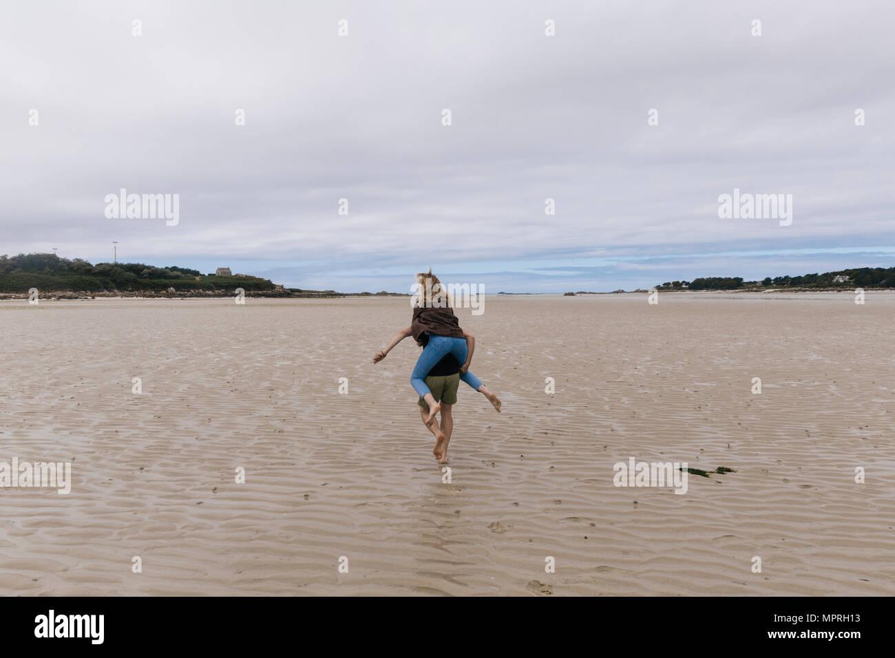 Francia, Bretaña, Guisseny, joven hombre corriendo llevando novia piggyback en la playa Imagen De Stock