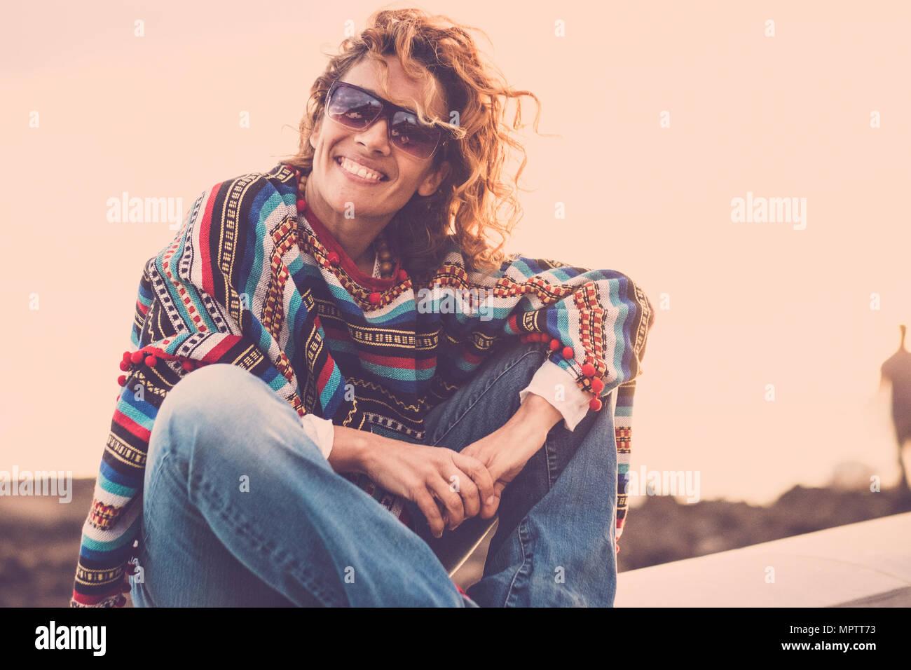 Lindo lindo dama con remolino cabello sonriendo mientras sentarse cerca de la costa del océano. poncho y ropa hippie para representar la libertad concepto sty vacaciones. Imagen De Stock