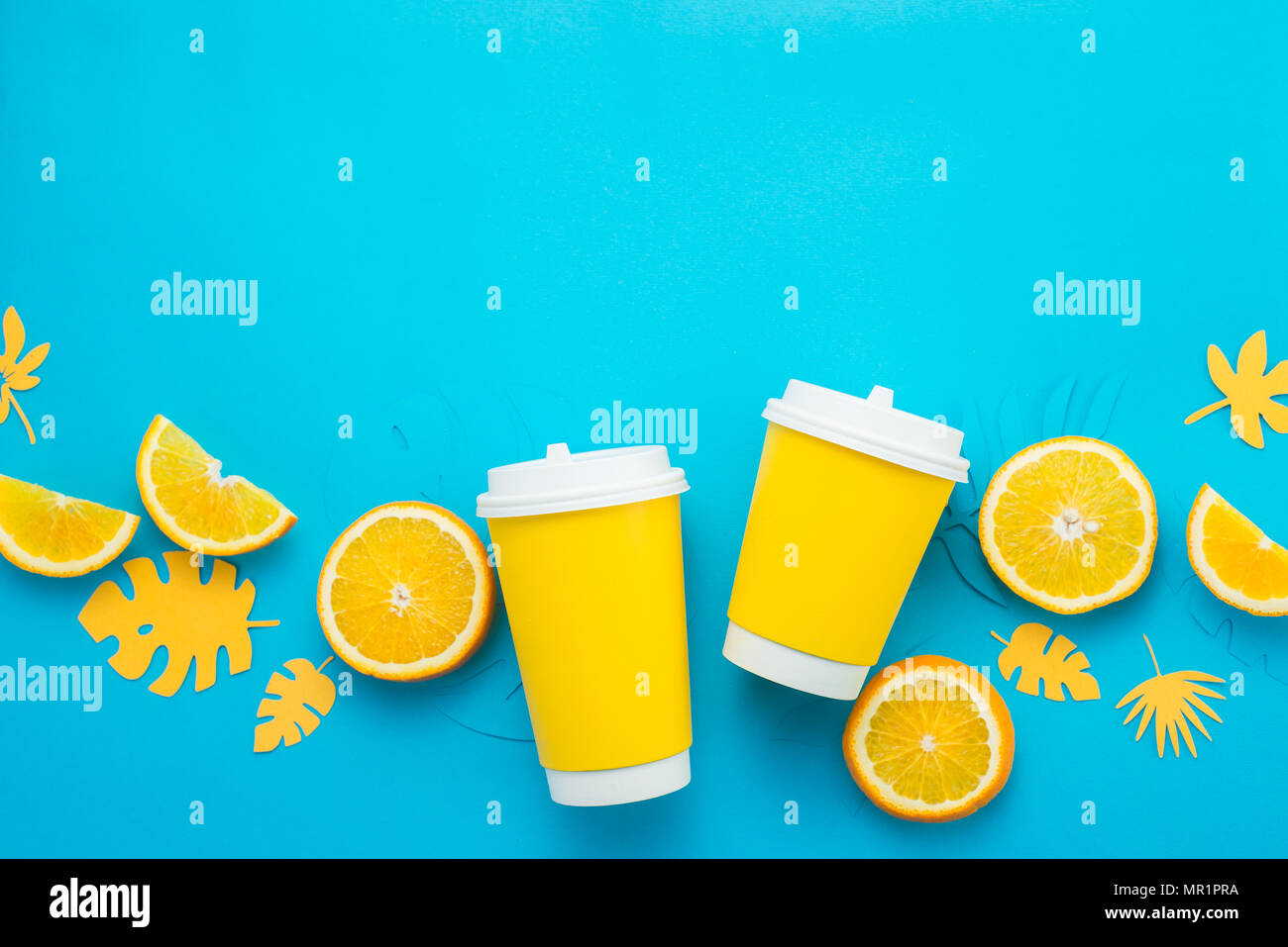 Tazas de papel con rodajas de limón y hojas tropicales sobre un fondo de color azul brillante. Copa de Verano para ir plana con copia espacio laical. Limonada desde arriba Imagen De Stock