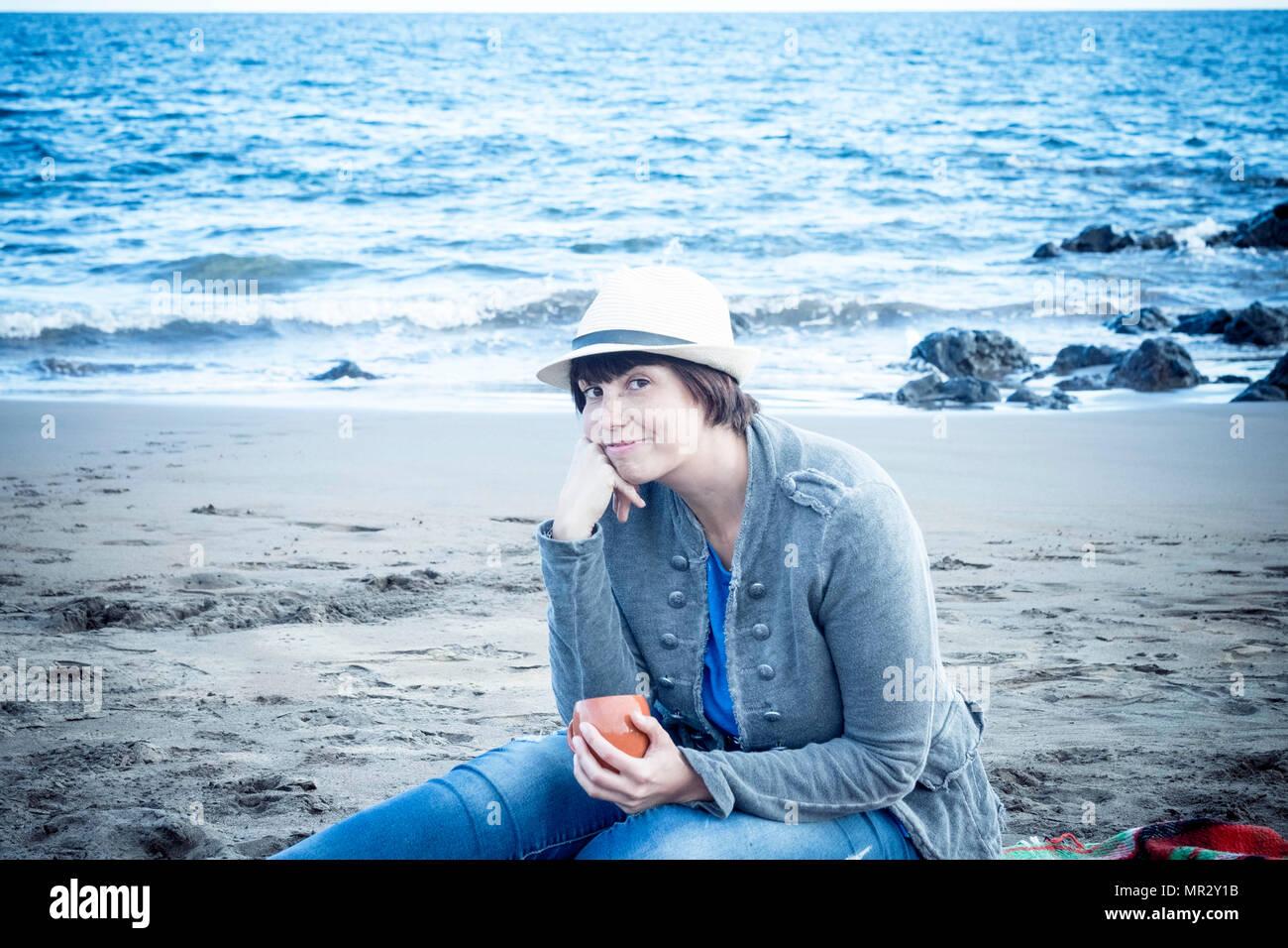 Preciosas chica sonriente con sombrero sentado en la playa en invierno. vacaciones bonito concepto de ocio al aire libre. Imagen De Stock