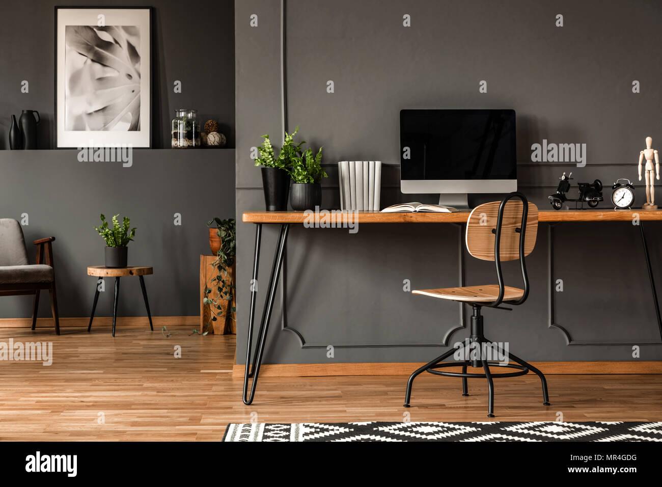 Foto real de un espacio abierto interior con paredes negras y moldeo. Área de trabajo con escritorio, silla y equipo en el primer plano y el salón con gris Imagen De Stock