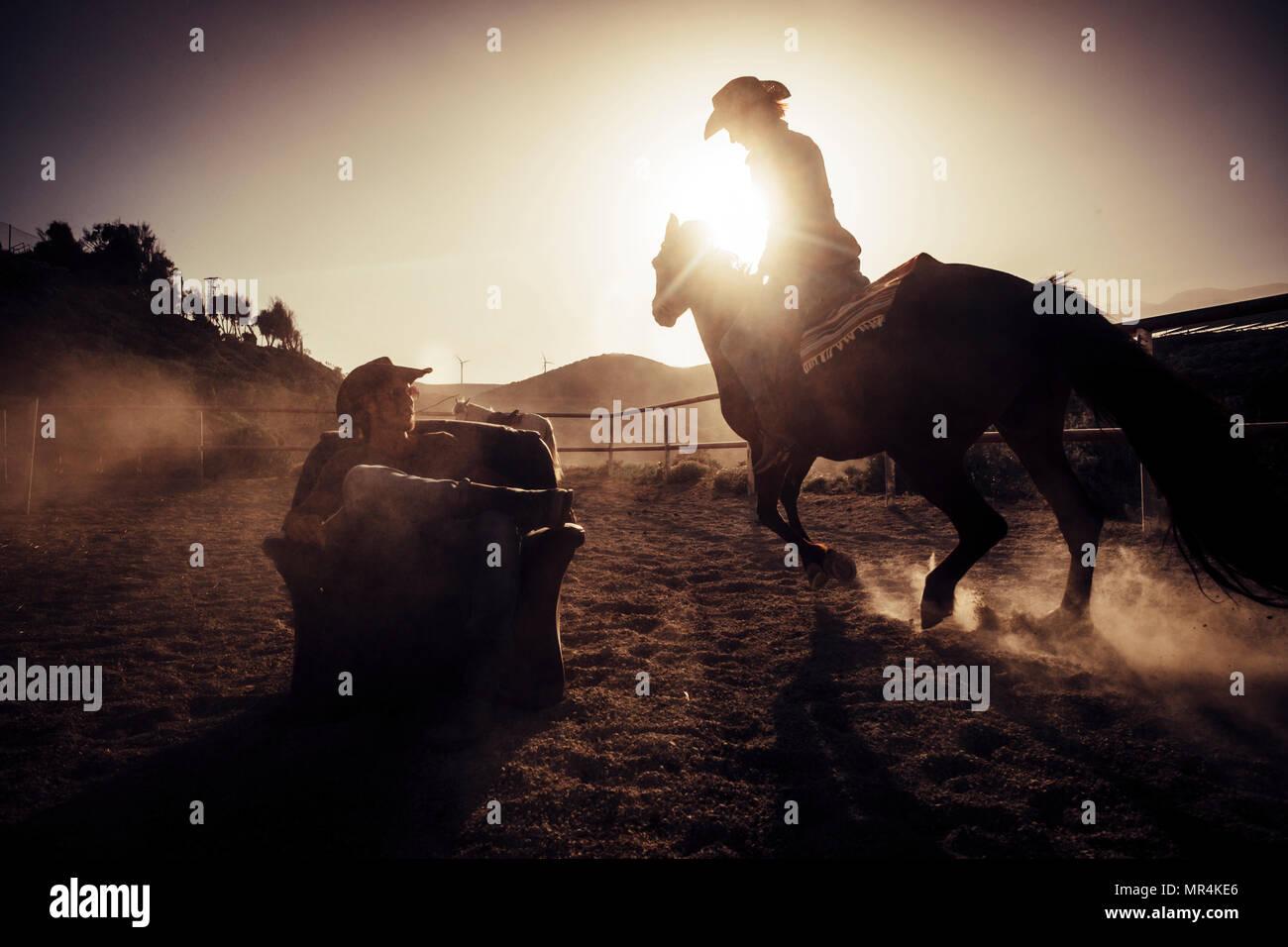 Concepto de héroe dramático y publicidad de imagen estilo cowgirl haciendo polvo a caballo cerca de un vaquero siéntese en una silla en medio de la pista. Foto de stock