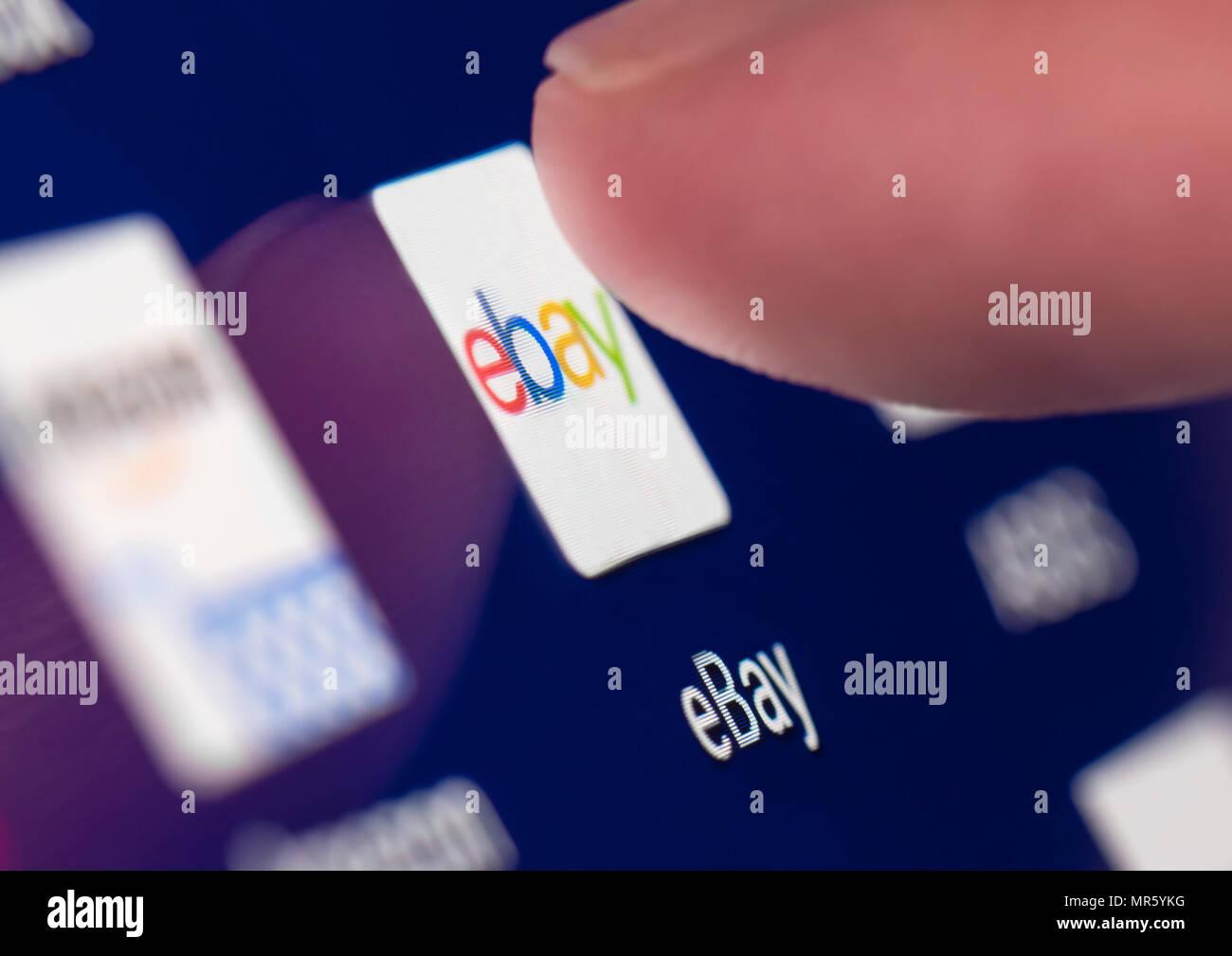 Dedo pulsando el icono de App de Ebay en un dispositivo móvil de pantalla táctil en un tablet o smartphone. Imagen De Stock