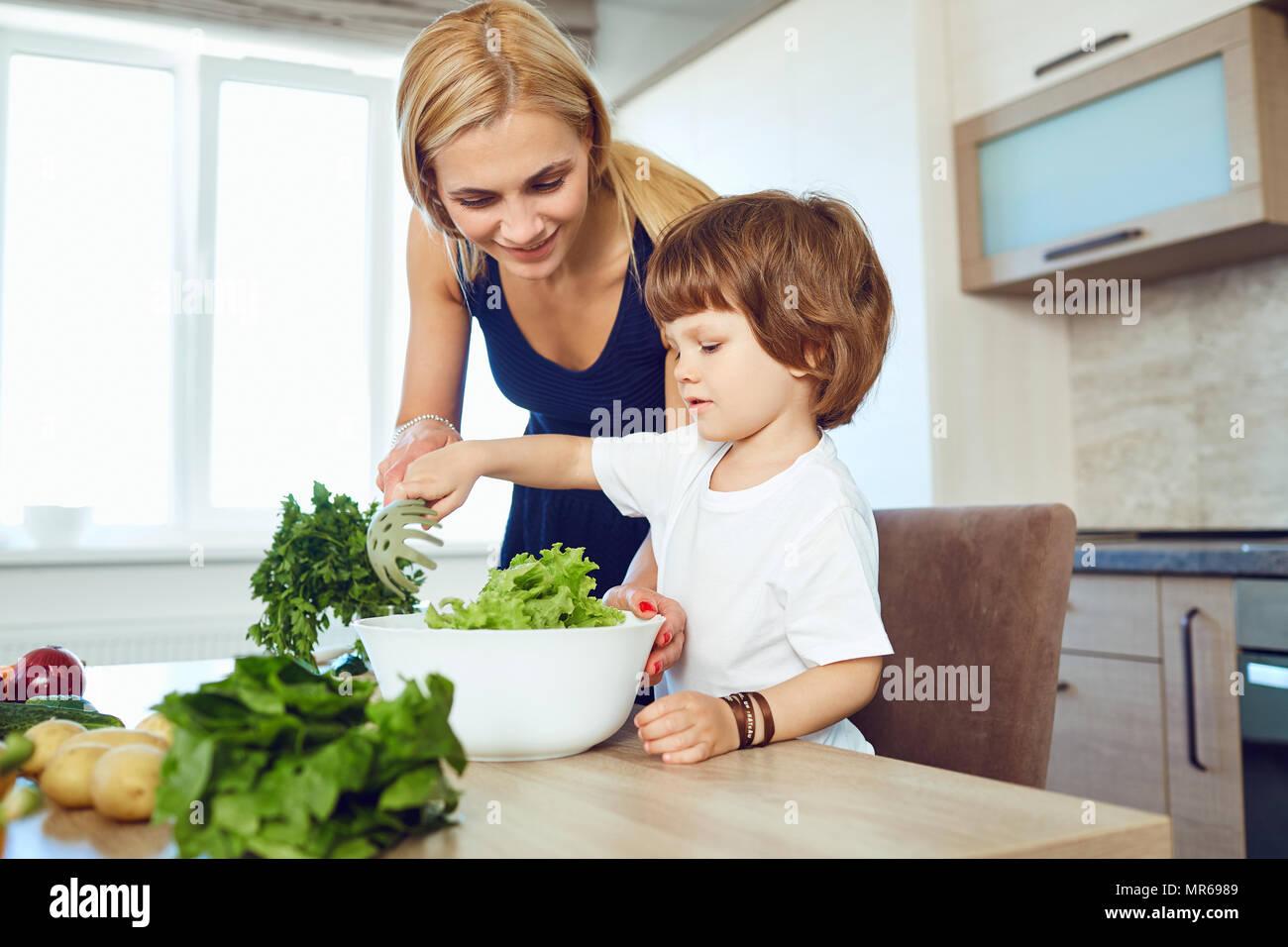 Mamá y su niño están preparando la comida en la cocina. Imagen De Stock