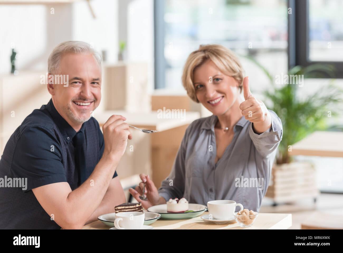 Mujer mostrando el pulgar hacia arriba para los dulces en el cafe Imagen De Stock