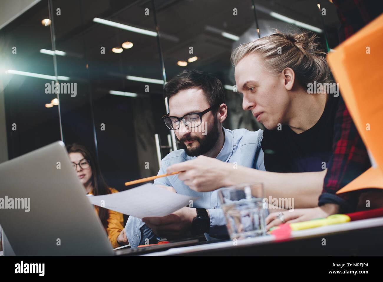 Equipo de jóvenes estudiantes de ingeniería está trabajando en un nuevo proyecto, discutir los diagramas en papel y ordenador portátil en un moderno espacio loft Foto de stock