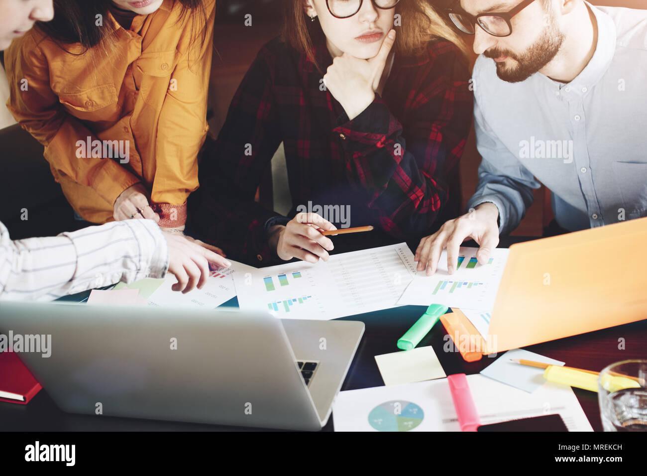 Manos humanas con papel, gadget y portátil durante el debate en la moderna oficina loft Imagen De Stock