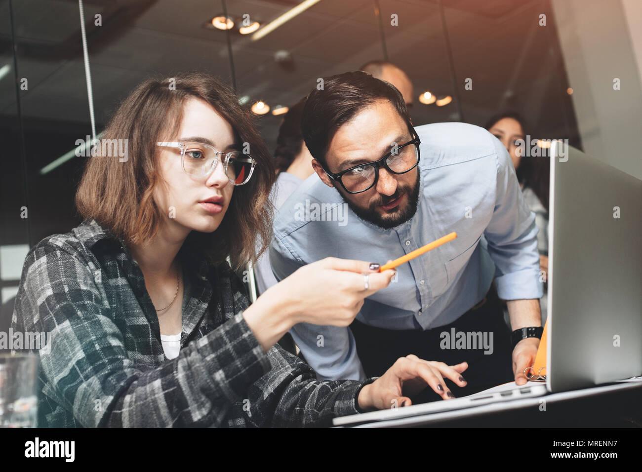Joven y bella mujer de negocios en vidrios con un lápiz en la mano muestra el análisis de proyecto a su socio comercial barbudo. Los jóvenes compañeros worki Imagen De Stock