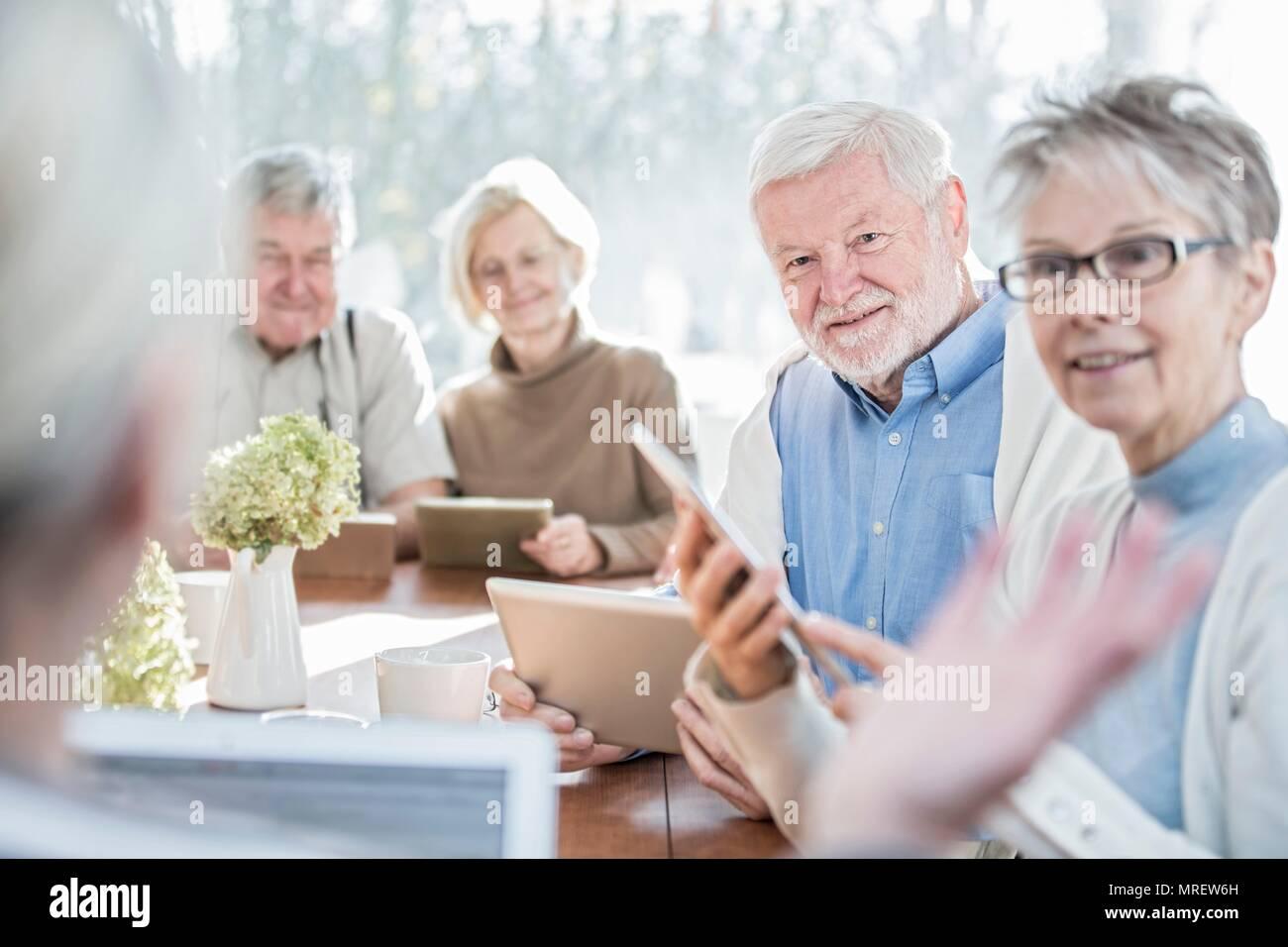Los adultos mayores cuidados en el hogar con tabletas digitales. Imagen De Stock