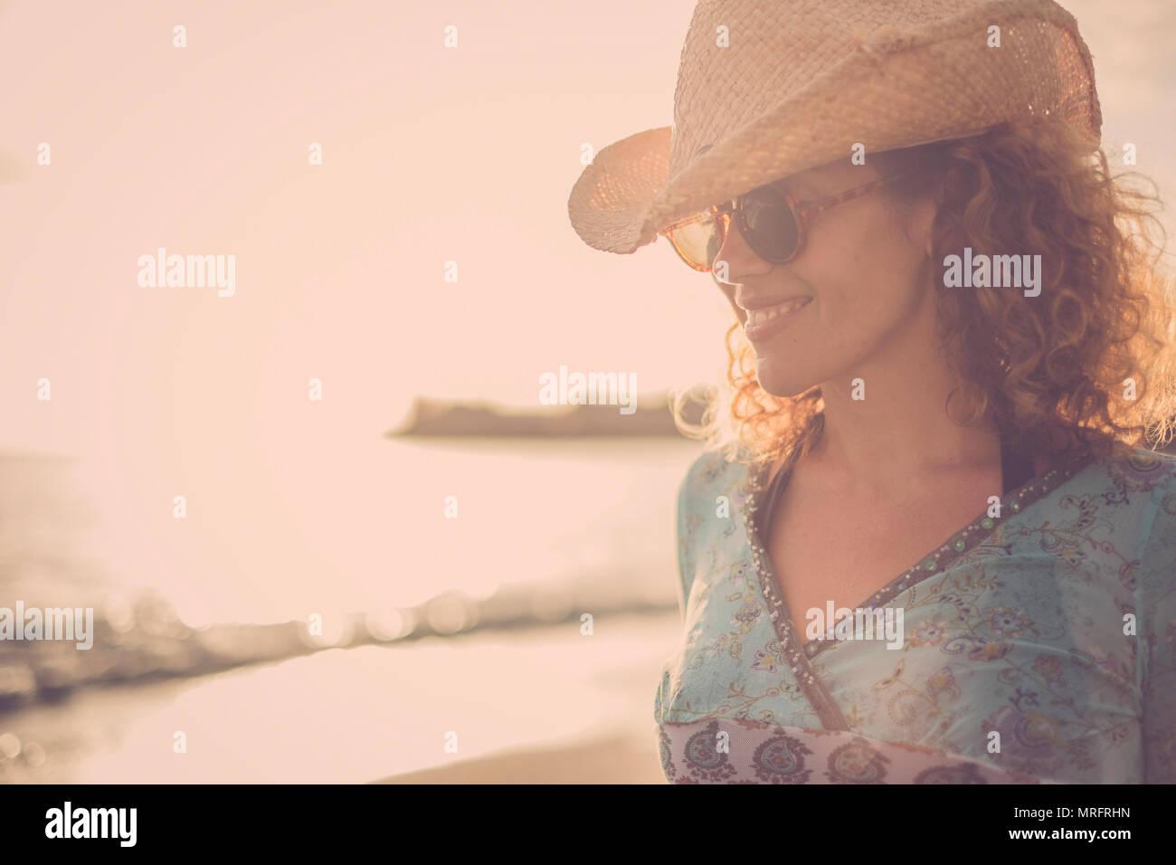 Bello y maravilloso cabello rizado rubio modelo edad media con sombrero de cowboy sonreír y posar en la playa con el sol de oro en el fondo de un color. Imagen De Stock