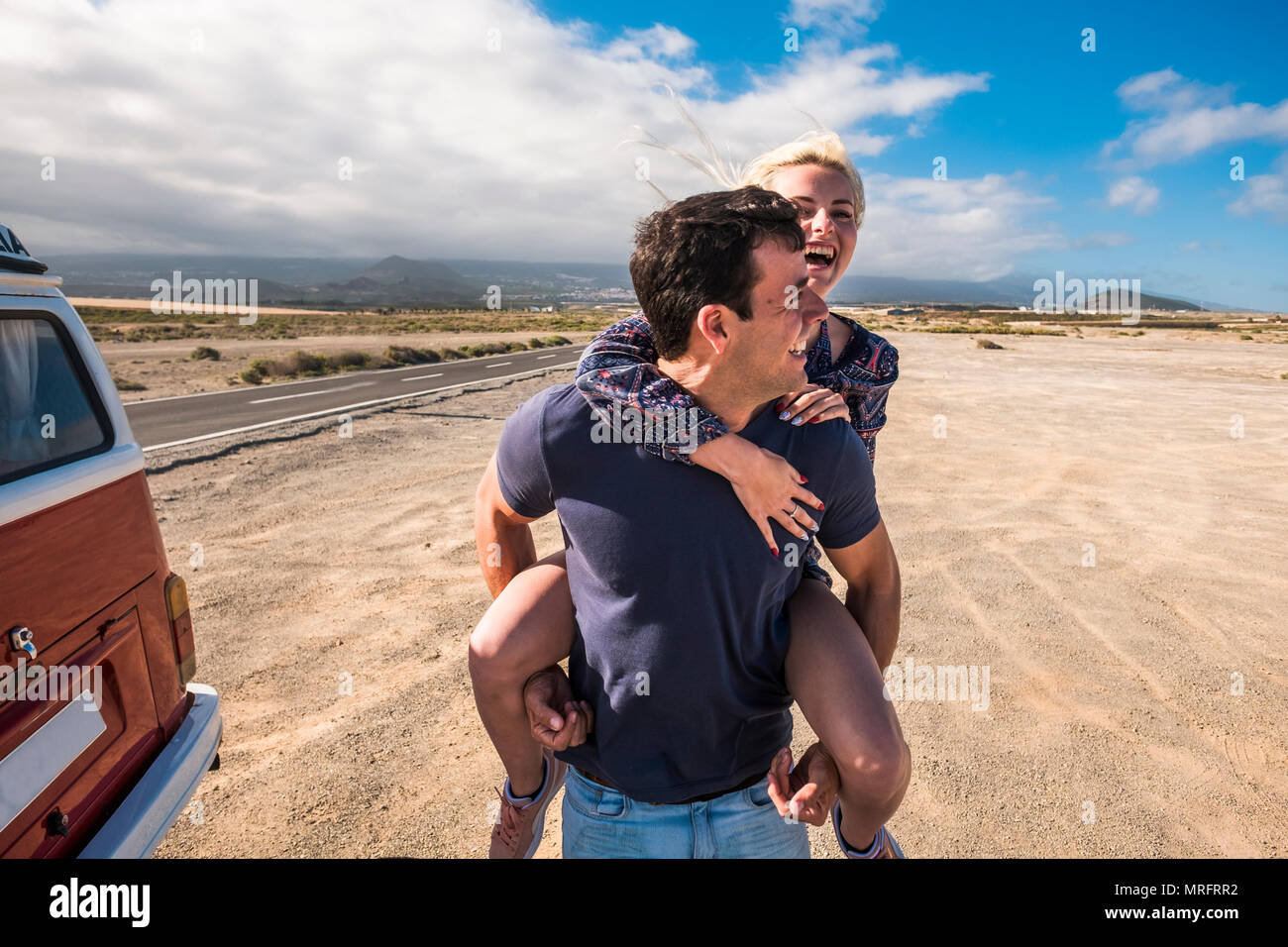 Bonito Bonito modelo caucasiano par en amor jugar y permanecer juntos en las actividades de ocio al aire libre, cerca de un largo camino que cruza el desierto en un viaje largo v Foto de stock