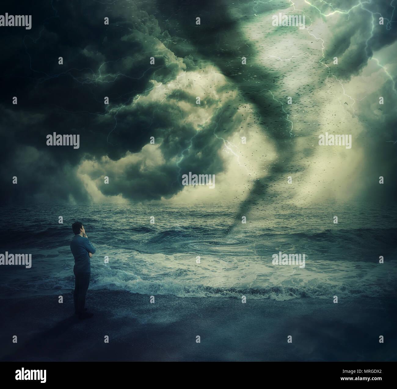 Pensativo empresario valiente postura sobre la orilla fornt de un poderoso tornado tormenta en el mar, causando daños y destrucción. Foto de stock