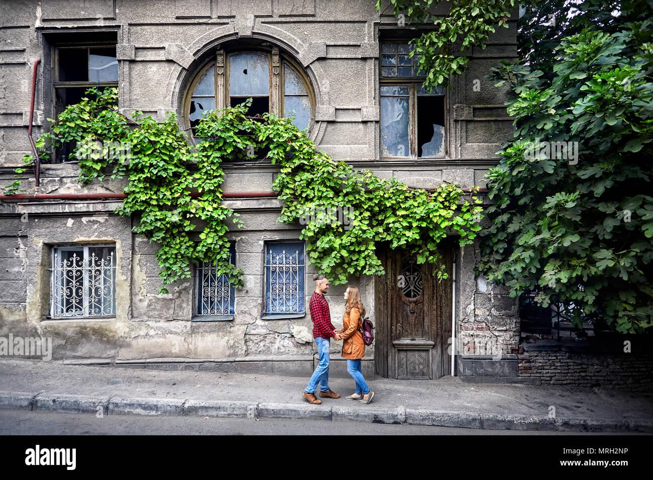 Feliz pareja de turista cerca de vintage casa con ventana redonda en viejas calles del centro de Tbilisi, Georgia Imagen De Stock