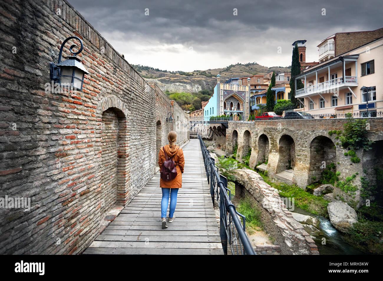 Mujer de turística chaqueta marrón caminando por las antiguas calles de baño sulfúrico público en el centro de distrito de Tbilisi, Georgia Imagen De Stock