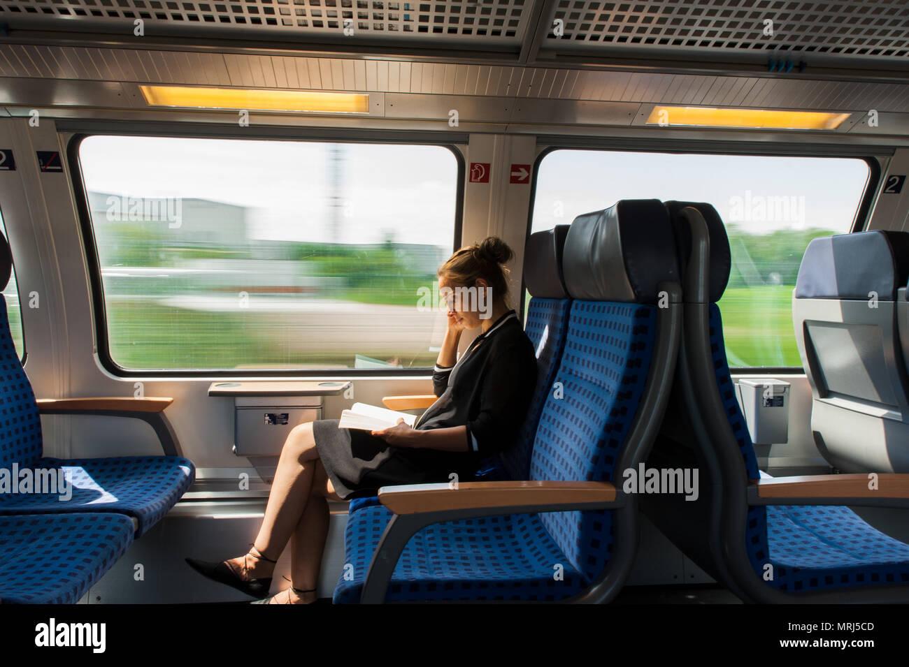 Mujer joven leyendo un libro mientras viaja en tren Foto de stock