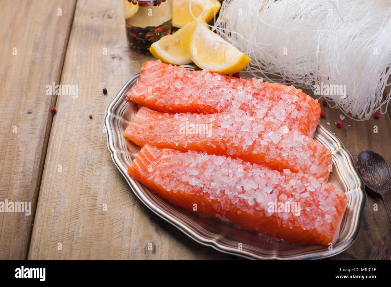 Filete de salmón crudo con pimienta y sal de molleja sobre papel de hornear tema rústico con copy-espacio. Imagen De Stock