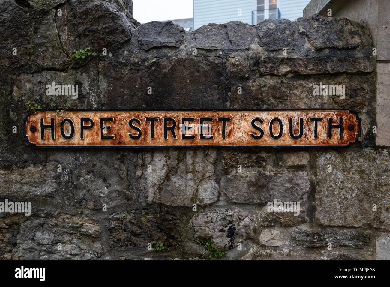 Hope Street South, una vieja y desgastada la oxidación de metales nombre de calle signo adjunta a un viejo muro de mampostería de piedra. Foto de stock