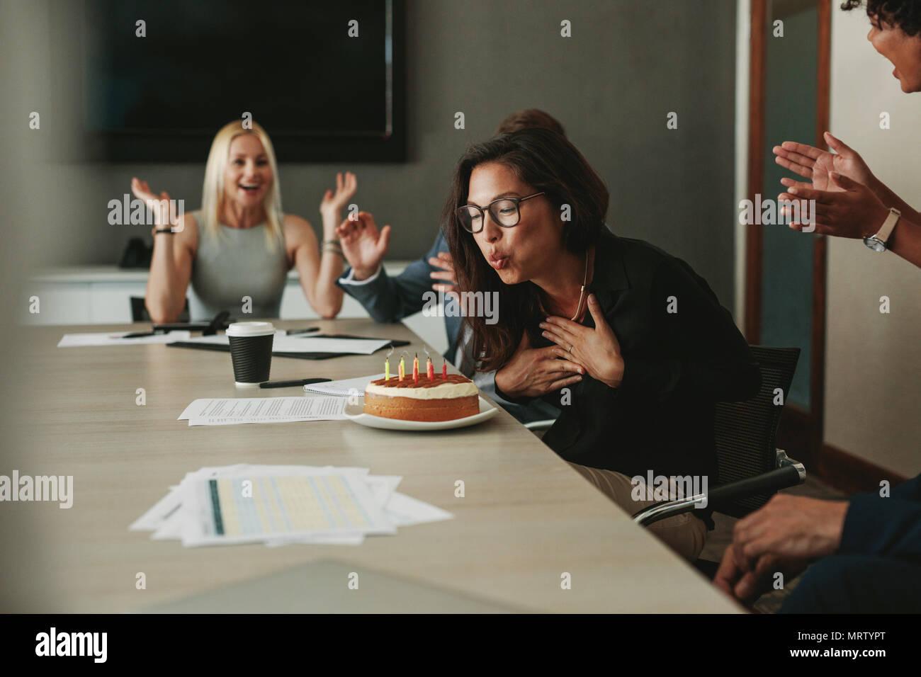 La empresaria soplando las velas en una tarta de cumpleaños en la oficina. Mujeres asiáticas asociar celebrando su cumpleaños con sus colegas en la oficina. Foto de stock
