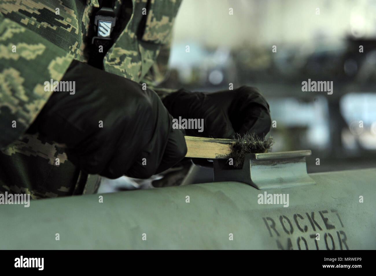 La Fuerza Aérea de los EE.UU Aerotécnico de Primera Clase, 20 de Lerum Ty Escuadrón de Mantenimiento de equipo técnico de municiones guiadas de precisión, utiliza un cepillo de alambre para quitar sólida película sobre un colgador de misiles AIM-9 Sidewinder en la base de la fuerza aérea Shaw, S.C., 27 de junio de 2017. La película de lubricante protege la percha cuando la munición se adjunta a un avión. (Ee.Uu. Foto de la fuerza aérea por Aerotécnico de Primera Clase Kathryn R.C. Reaves) Foto de stock