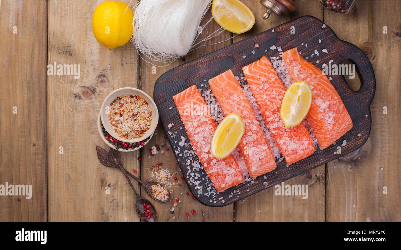 Filete de salmón crudo con pimienta y sal de molleja sobre papel de hornear tema rústico con copy-espacio. Sentar plana Imagen De Stock