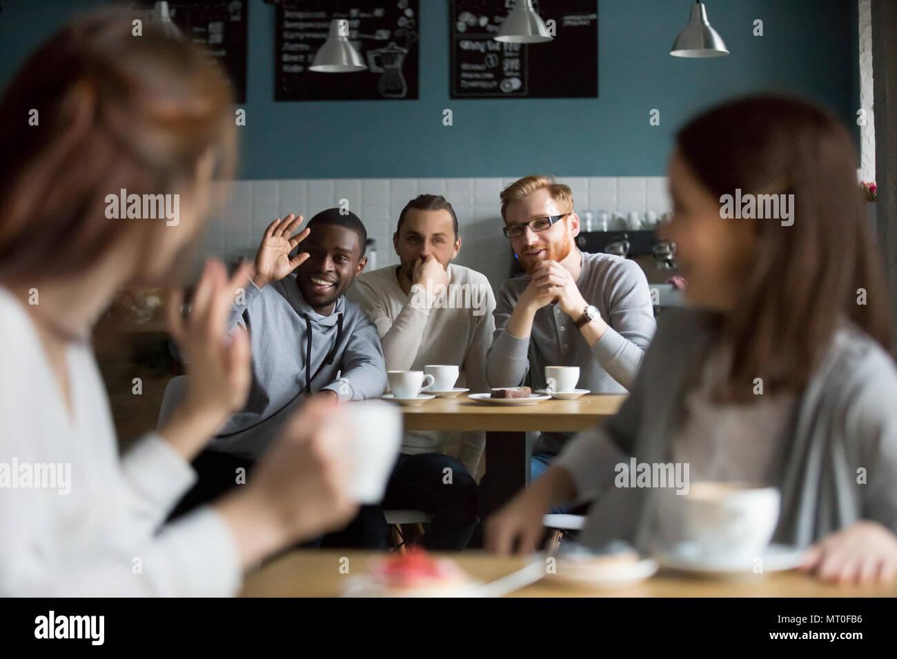 Hombre sonriente africanos agitando la mano saludo niñas reunión de café Imagen De Stock