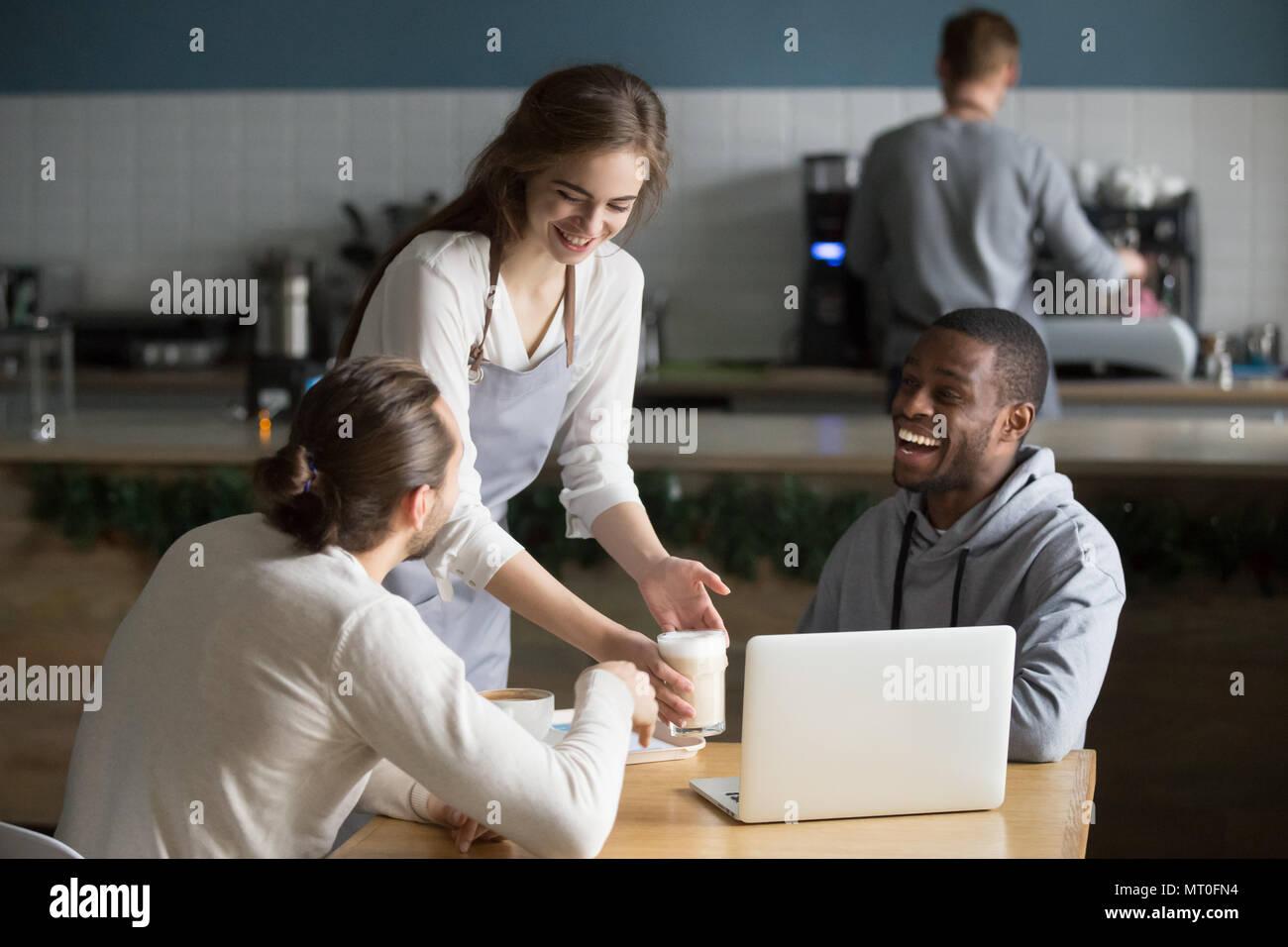 Camarera y visitantes multirraciales riendo en chiste gracioso en el café Imagen De Stock