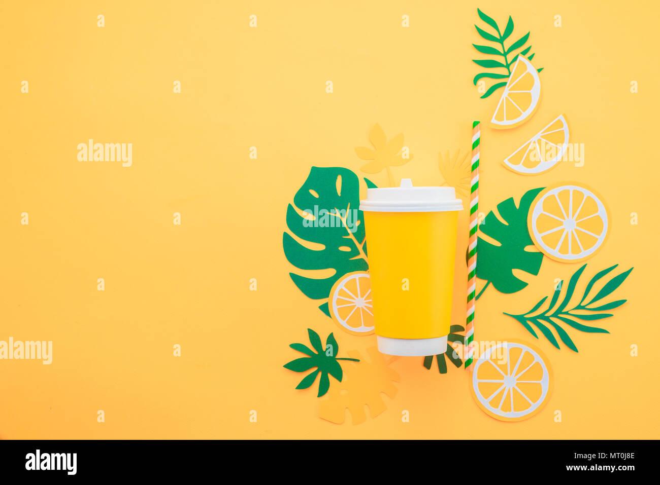 Vaso de papel desechable sobre un fondo amarillo con hojas tropicales y las rodajas de naranja sobre un fondo de color amarillo brillante. Copa de Verano colorido concepto con p Imagen De Stock