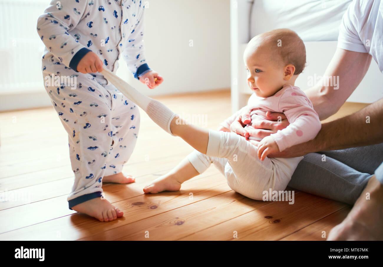 Padre y niño niños sentados en el piso en casa a la hora de acostarse. Imagen De Stock