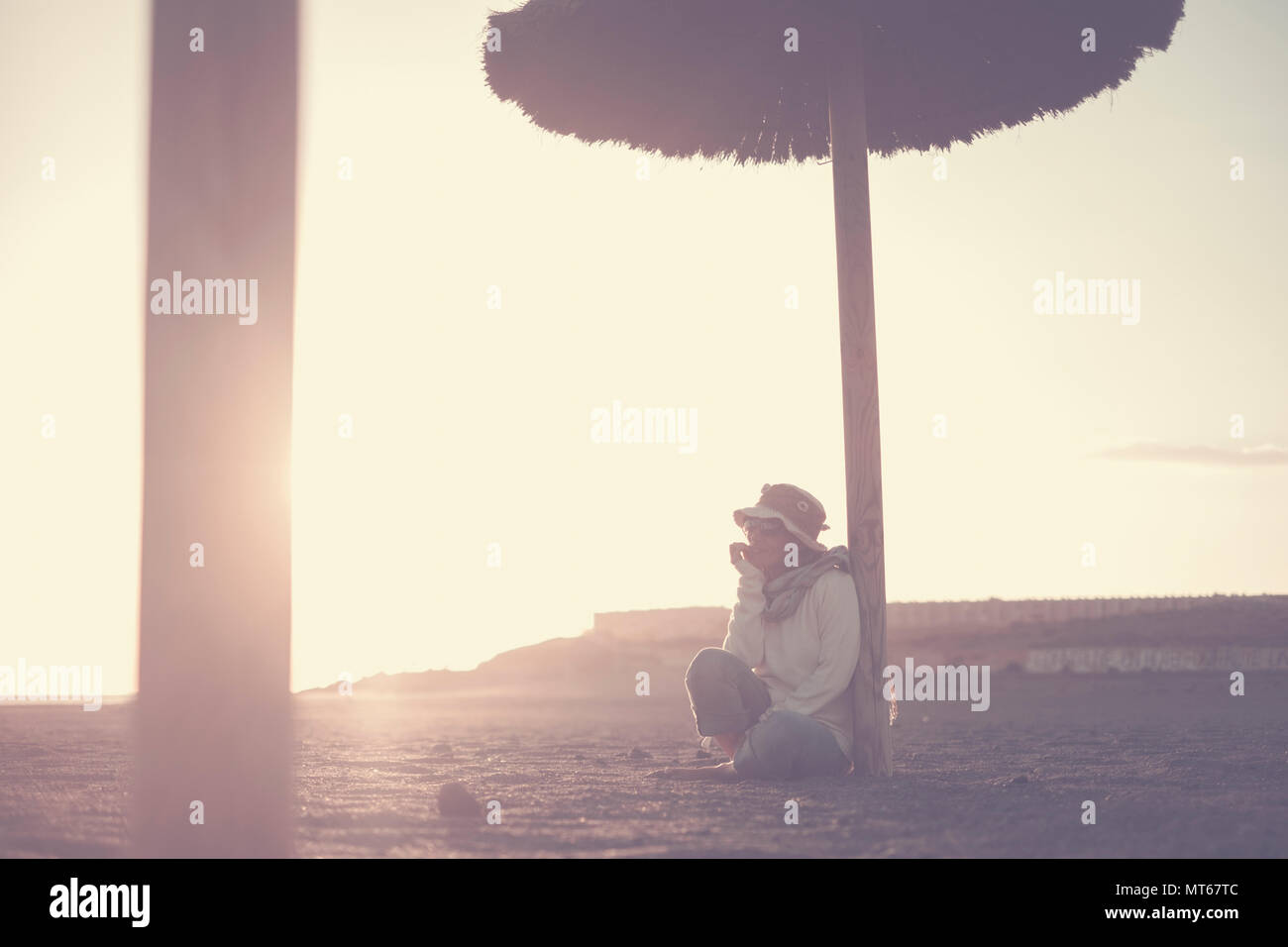 Hermosa hembra solitaria de mediana edad sentarse en la playa con un asombroso atardecer luz sobre el fondo. Tenerife pintoresco lugar para vacaciones verano leisu. Foto de stock