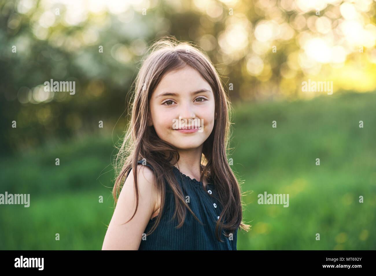 Una niña pequeña de pie fuera en la naturaleza. Imagen De Stock