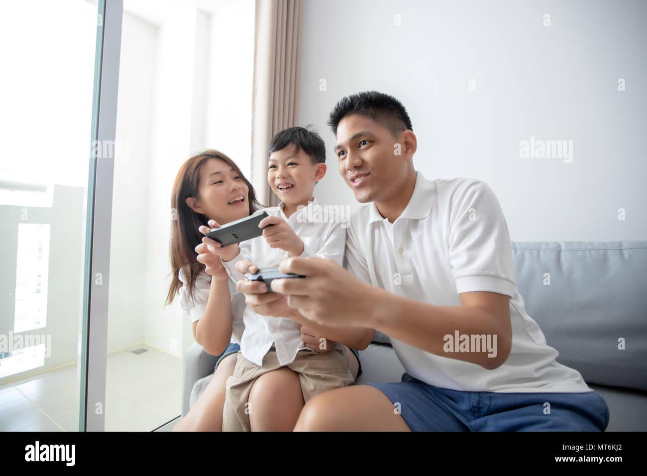 Familia de Asia divertirse jugando juegos de la consola del equipo juntos, padre e hijo tienen el auricular controladores y la madre está animando a los jugadores. Imagen De Stock