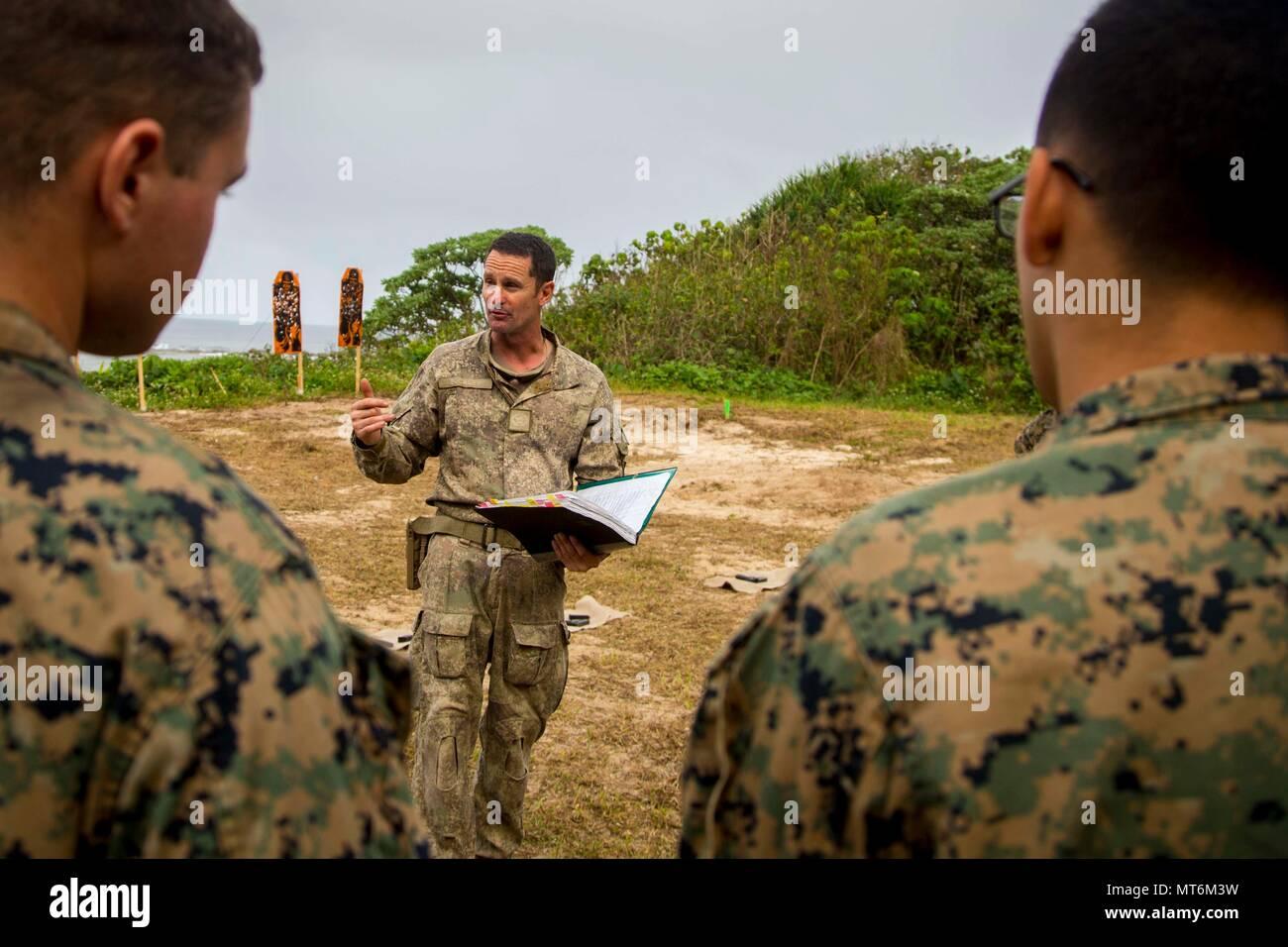 El Sargento del Ejército de Nueva Zelanda. Gral. Paul Buckley, sargento mayor de la compañía para la compañía Delta, explica a los Marines de Estados Unidos con el tercer batallón de Marines 4adjunta a la Task Force 17 Moana Koa, arma las reglas de seguridad antes de participar en un rango de fuego vivo durante el ejercicio TAFAKULA, en la isla de Tongatapu, Tonga, el 21 de julio de 2017. Ejercicio TAFAKULA está diseñado para fortalecer las militares, y las relaciones entre la comunidad de Tonga las Fuerzas Armadas de Su Majestad, el ejército francés de Nueva Caledonia, la Fuerza de Defensa de Nueva Zelandia, y las Fuerzas Armadas de los Estados Unidos. (Ee.Uu. Marine Corps photo by MCIPAC Combatir la cámara Lance Cpl. Foto de stock